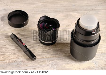 Fisheye Lens, Telephoto Zoom Lens And Pen For Lens Cleaning At Table.