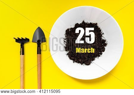 March 25th. Day 25 Of Month, Calendar Date. White Plate Of Soil With A Small Spatula And Rake On Yel