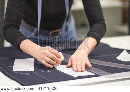 Seamstress Workplace. Woman Seamstress Makes Pattern With Chalk On Fabric For Sewing Clothes In Tail