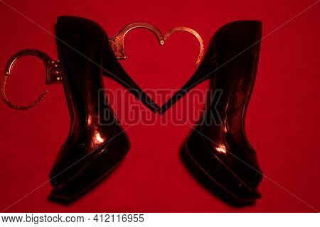 Bdsm, Sexual Behaviour Concept. Red High Heeled Shoe With Handcuffs