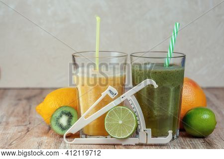 Tall Glasses Of Kiwi And Spinach Smoothies In A Row Surrounded By Fruits And Caliper On A Wooden Tab