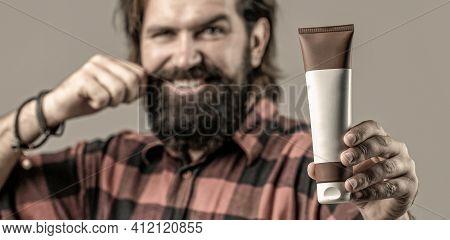 Man Holds Black Bottle Of Shampoo Or Shower Gel. Shampoo Conditioner For Men. Expert Care For Demand