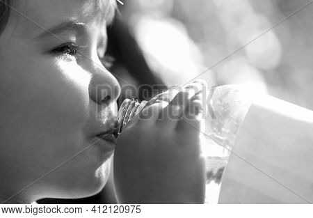Young Boy Holding Drink Fresh Water Bottle. A Child Drinks Water From A Bottle, Baby Health. Portrai