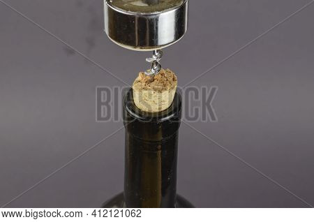 Wine Bottle, Corkscrew And Broken Cork On A Gray Background. The Corkscrew Is Screwed Into The Broke