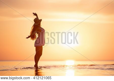 Happy Slim Ladies Silhouette Is Dancing At Tranquil Sunset Beach