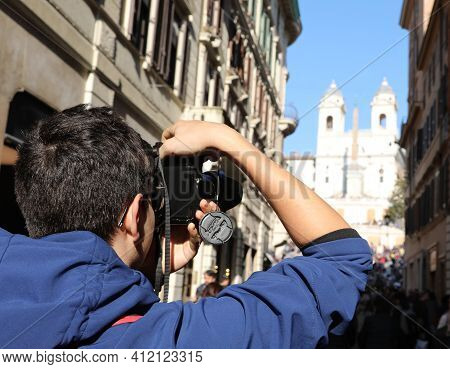 Young Photographer Taking A Souvenir Photo At The Church Of Trinita Dei Monti In Rome Capital Of Ita