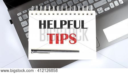 Business Concept - Top View Notebook Writing Helpful Tips On Laptop