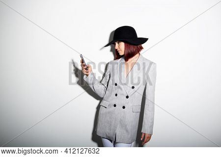 Young stylish woman using smartphone, indoor portrait over white. Fashion modern girl wearing grey jaket and black hat texting on her mobile phones