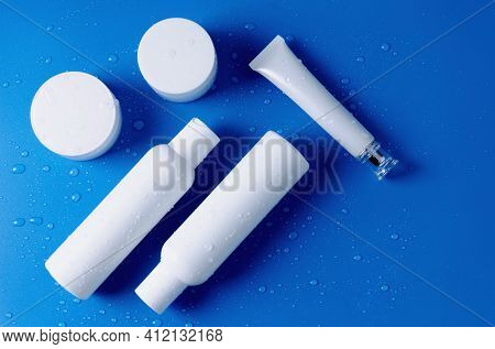 White Cosmetic Bottles, Tubes, Jars On A Blue Background With Water Drops. Cosmetic Products For Ski