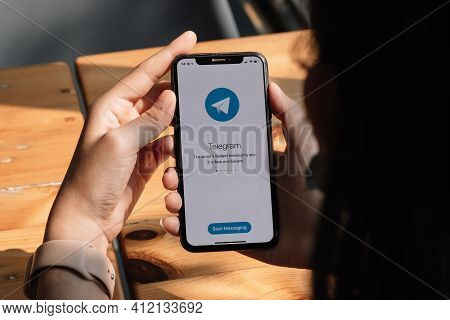 Chiang Mai, Thailand, Mar 7, 2021 : Woman Hand Holding Iphone X With Social Networking Service Teleg