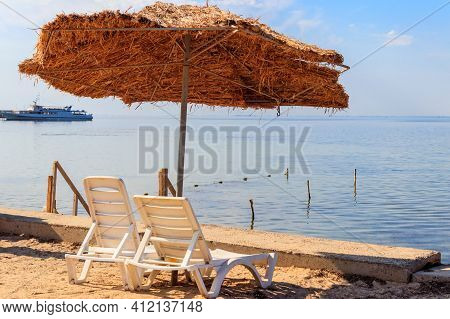 Two Chaise Lounges Under A Sun Umbrella On Tropical Beach. Concept Of Rest, Relaxation, Holidays, Re