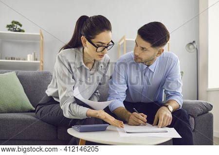 Young Husband And Wife Sitting On Couch, Calculating Expenses And Planning Family Budget