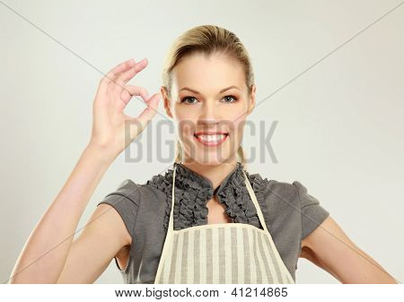 Beautiful happy young blond woman wearing kitchen apron and showin g ok , isolated on white background