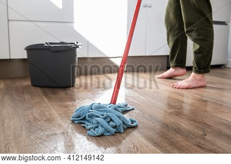 Barefoot Woman Mopping Her Home\'s Wooden Floor.cleaning Concept