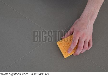 Close Up Of Woman's Hand With Yellow Scouring Pad Cleaning Kitchen Counter Top.copy Space.cleaning C