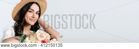 Pleased Young Woman In Straw Hat Holding Bouquet Of Spring Flowers Isolated On White, Banner.