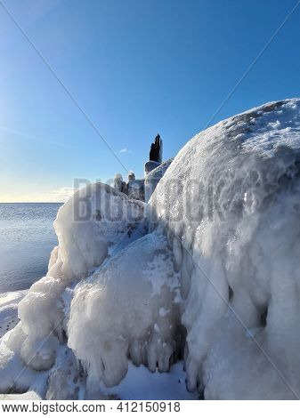 Winter Coast Of The Baltic Sea With A Stone Pier Which Is Covered With Ice At The End Of The Pier. B