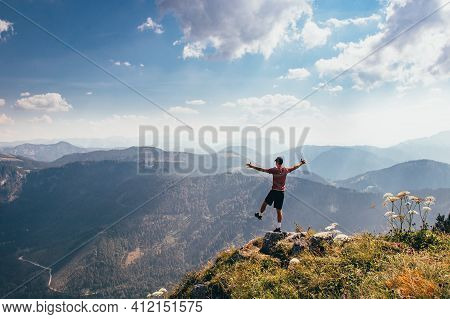 Balancing On One Leg Over An Abyss In Lower Austria. Beginning Of The Western Alps. A Young Athlete