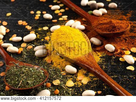 Wooden Spoons With Multicoloured Seasonings On A Black Textured Table. Background For Kitchen