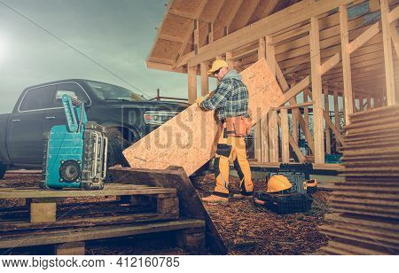 Contractor Worker Moving Piece Of Plywood In Newly Built Wooden House Construction Site. Industrial