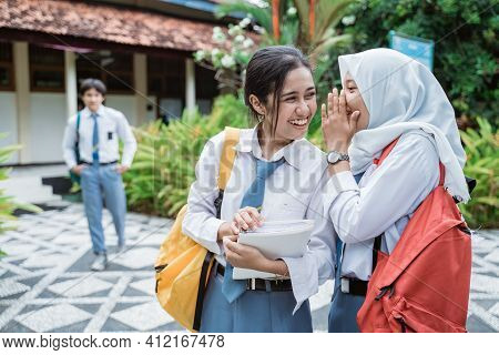 A Female High School Student Wearing A Veil Whispers To A Smiling Female High School Student With A