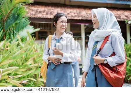 Close Up Of Two High School Girls Laughing Wearing School Bags And Carrying Books Walking With Schoo