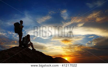 Silhouettes of two tourists with backpacks relaxing on top of a mountain and enjoying sunset view