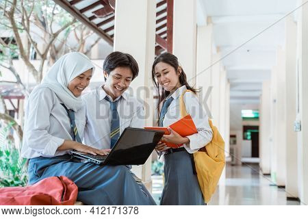 A Boy, Girl, And Girl In A Veil In High School Uniform Doing Group Assignment Using A Laptop Compute