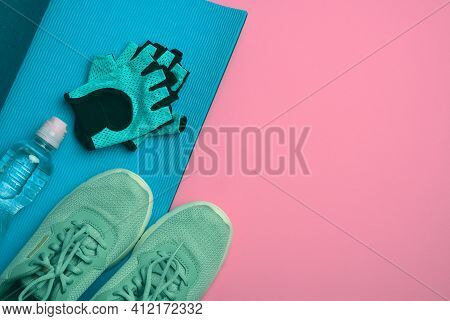 Pair Of Sports Sneakers And A Bottle With Mineral Water On A Pink Background, Top View, Copy Space