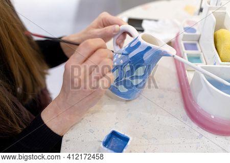 An Unrecognizable Female Ceramist Paints A Clay Milkman With A Brush. Ceramic Art Concept. Selective