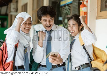 Close Up Of Three Students In High School Uniform Enthusiastically Use One Smartphone To View Joint