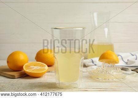 Freshly Squeezed Lemon Juice On White Wooden Table