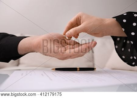 Woman Giving Wedding Ring To Her Husband Over Divorce Papers Indoors, Closeup