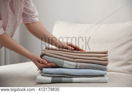 Woman With Folded Cashmere Clothes Indoors, Closeup
