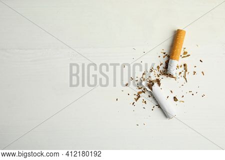 Broken Cigarette On White Table, Flat Lay With Space For Text. Quitting Smoking Concept