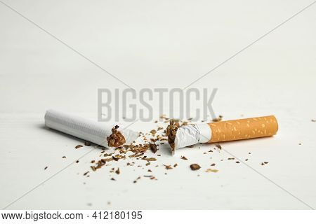 Broken Cigarette On White Table, Closeup. Quitting Smoking Concept