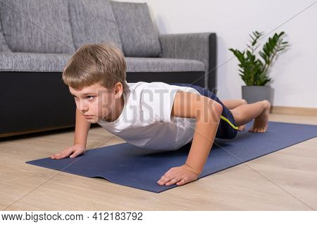 Boy On Yoga Mat At Home Holding Plank Pose. Child Physical Activity On Quarantine Healhty Lifestyle