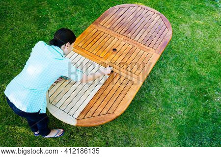 Woman Painting Wooden Exotic Wood Table In The Garden With A Paintbrush