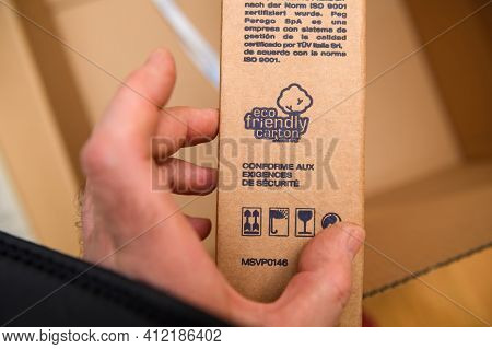 Paris, France - Mar 10, 2021: Pov Male Hand Holding Cardboard Box With Detail Of Eco Friendly Carton