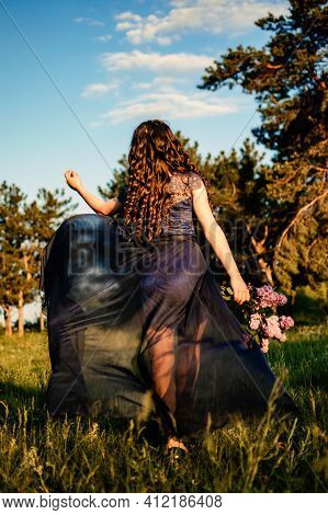 Party Graduation Prom Fairytale Concept. Beautiful Brunette Young Woman In Blue Prom Dress With Lila