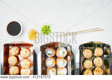 Take Away Sushi Rolls In Containers, Philadelphia Rolls And Baked Prawn Rolls Set, On White Stone  B