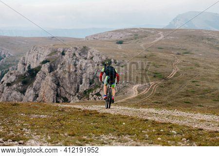 Back Male Cyclist Biking On Mountain Path On Mountain Bike
