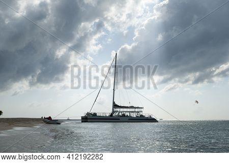 The Tourist Catamaran By Cozumel Island Beach Under Dark Cloudy Sky (mexico).