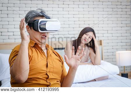 Concept Of Family Problems. An Elderly Asian Husband Is Very Addicted To Vr Games. Makes The Young W