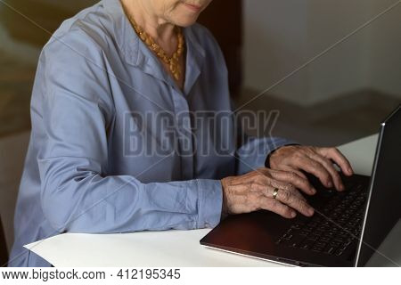 Elderly Woman Wrinkled Hands Typing On A Laptop. Online Education For Seniors. Surfing Internet.