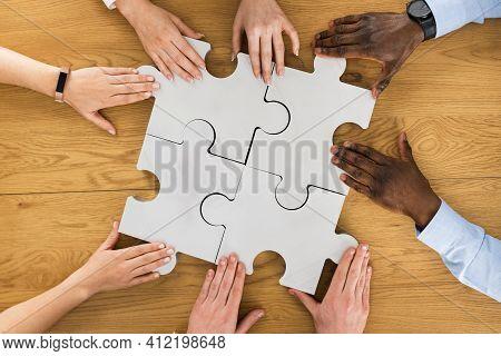 Teamwork Meeting Hands Solving Jigsaw Puzzle. Overhead View