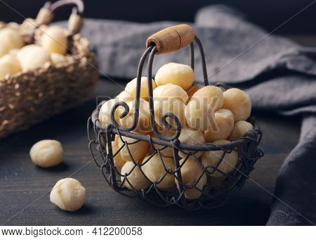 Macadamia nuts isolated on a dark wooden background