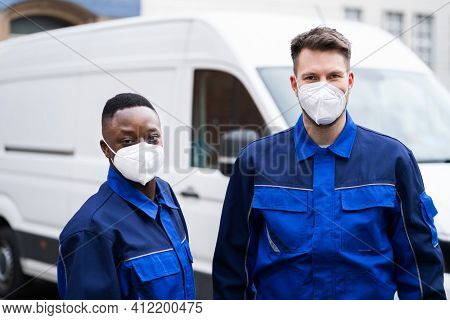 Electrician Technician Or Plumber In Workwear And Face Mask Near Van