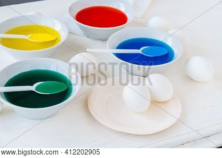 Getting Ready For Easter With Liquid Food Coloring. Different Colors In Different Bowls, Egds On Whi