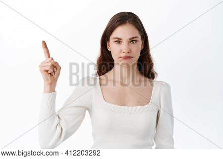 Disappointed And Sad Girl Pointing At Unfair Bad Thing, Points Up At Logo On Top And Pouting Upset,